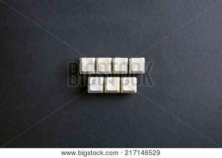 Year end 2017. Flat lay view from above on the table with computer keyboard keys buttons on a dark background. New Year concept.