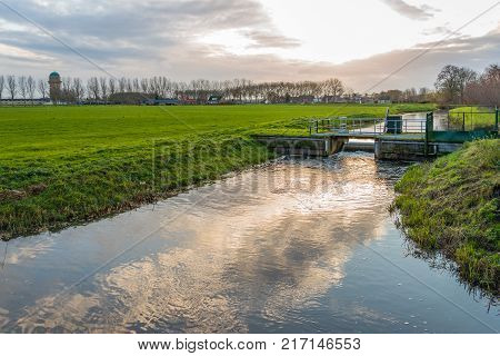 Dutch polder landscape in backlit on an autumnal afternoon. In the ditch is a small weir to manage the water.