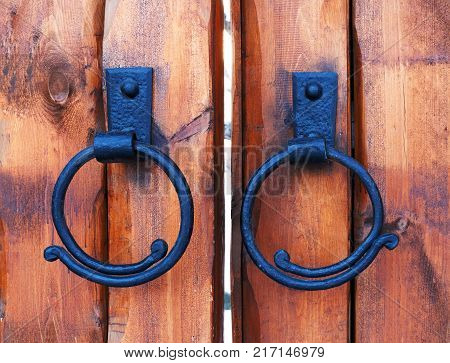 Wooden castle gate. Cast iron antique door handle ring on wood door. Door handles vintage or iron ring.