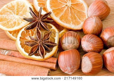 Hazelnuts with cinnamon anise and orange slices on a cutting board