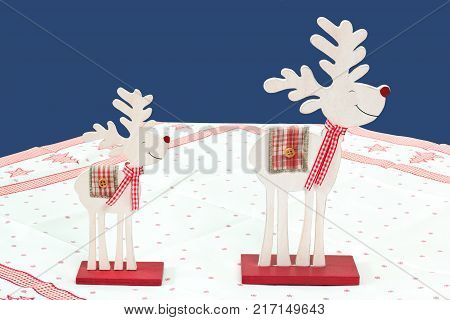 two reindeers of wood over blue background