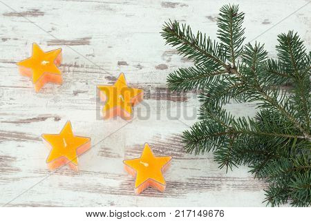 yellow star shaped candles with fir branch