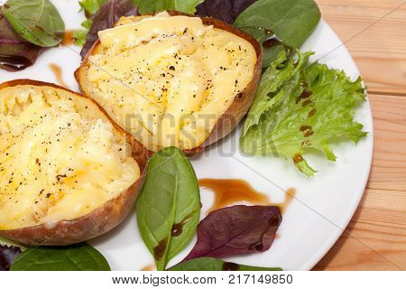Healthy baked potatoes with low fat flamed cheese and baby leaf salad with balsamic dressing. Close up of delicious easy potato slimmer food meal.