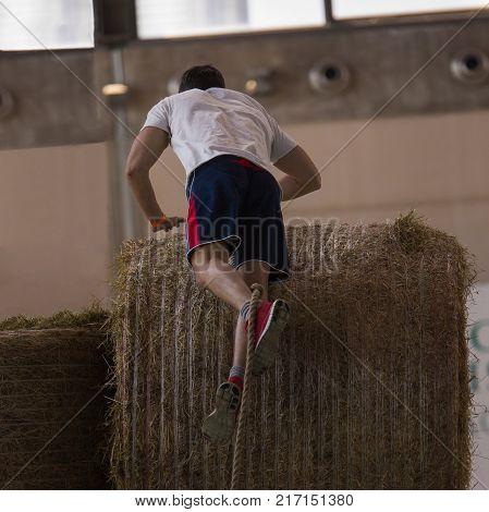 Indoor Hay Bale Obstacle Running Contest: People Climb Bale With Rope