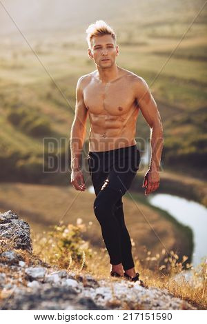 Handsome bare-chested man walking up hill during his training in nature.