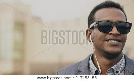 Steadicam shot of Young african american businessman listening to the music on his smartphone outdoors