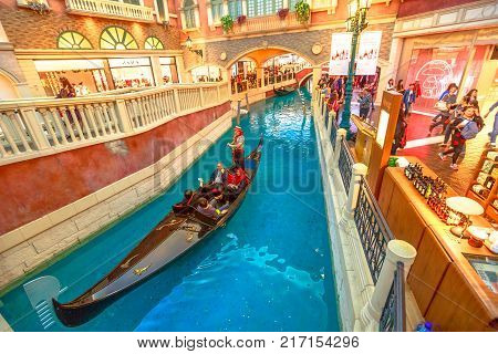 Macau, China - December 9, 2016: gondolier sings famous italian songs to tourists during a romantic ride in an authentic gondola down Grand Canals of Shoppes at the Venetian Luxury Hotel and Casino.