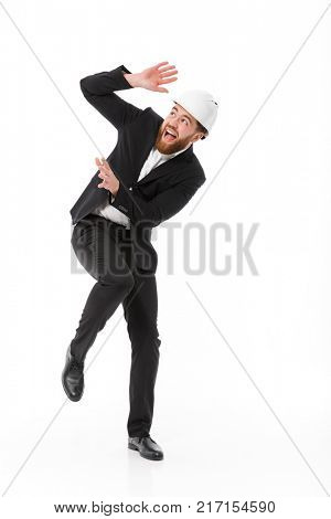 Full length image of Scared bearded business man in protective helmet covering himself over white background