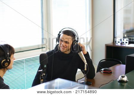 Cute female radio host and funny guy with headphones and talking are direct inclusion of radio, sitting in chair in radio studio. In office ponoramic large windows on desktop are microphones and mixing consoles, broadcast processor, special devices