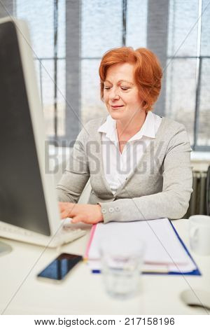 Senior business woman as typist working concentrated