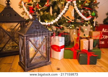Christmas Scene. Holiday Greeting Card Design. many gifts and a lantern stand near the New Year tree on the wooden floor of the house