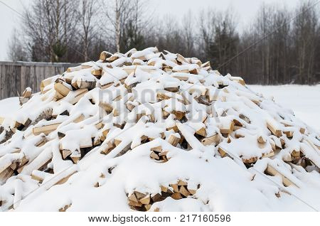 Winter background texture pattern with stacked dry chopped firewood logs covered with snow. Firewood pattern