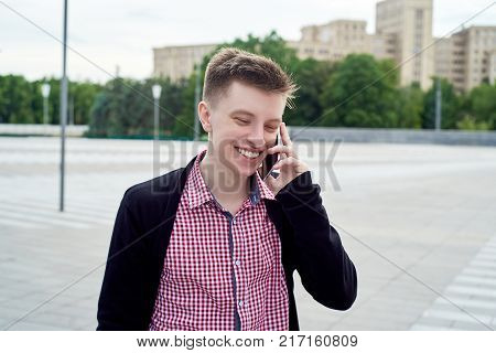 Happy smiling young man in plaid shirt and jacket walking in the city and talking on cell phone outdoors free space. Student with mobile smart phone