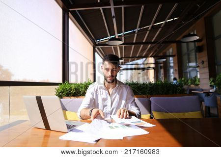 Lucky successful manager working with laptop and documents with diagrams at table indoors. Young gladden man enjoying good job and result, looking at cam and gesticulating yes. Concept of prosperous high class professionals and using modern devices