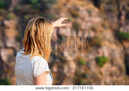 Beautiful woman points to horizon while travelling in canyon in Ranthambore tiger reserve, India. Wanderlust concept poster
