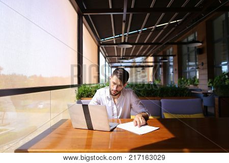 Inventory strategist solving problems and using laptop at cafe table. Clever hardworking man dressed in white shirt working with papers. Concept of  analyzing model forecast  to design contingency plans and catalog displays to make successful