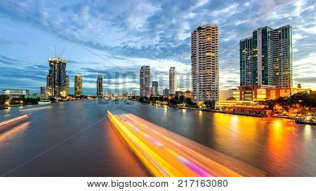 Bangkok city - Beautiful sunset curve Chao Phraya River long exposure light Cityscape urban of Bangkok city at night panorama landscape Thailand
