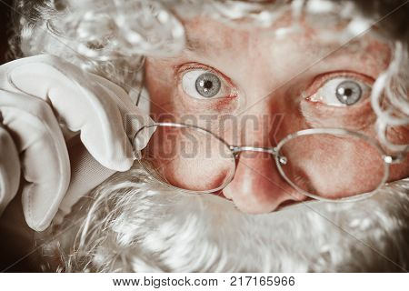 Portrait of Man in Santa Claus Costume - with a Luxurious White Beard, Santa's Hat and a Red Costume at red studio background. The face close up