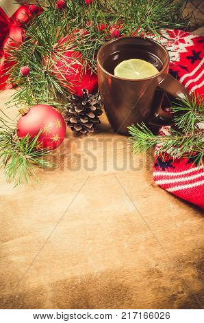 Cup of hot tea with lemon and warm woolen knitted scarf festive Christmas decorations on a vintage wooden board. Holidays at home. Winter time. Selective Focus.