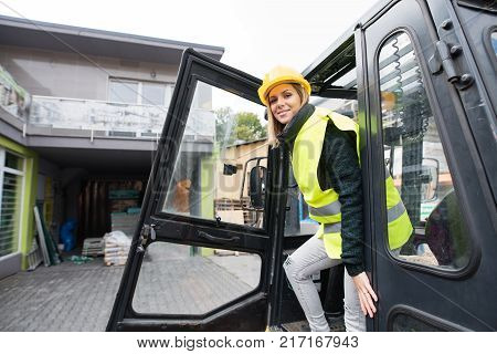 Woman forklift truck driver in an industrial area. A woman getting out of the fork lift truck.
