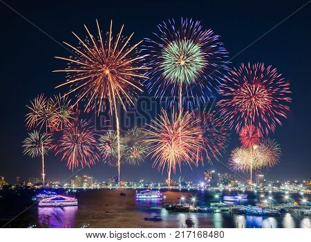 Fireworks over cityscape by the beach, sea or ocean surrounding with hotels restaurant and service boats and cruises during blue twilight time for celebrating New Year eve and special occasion on holidays