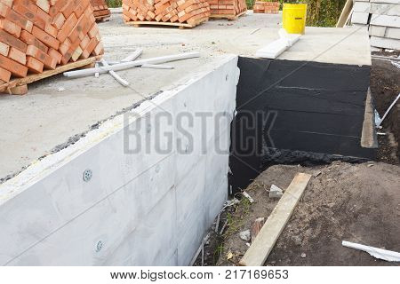Waterproofing house foundation with bitumen and styrofoam rigid foam insulation against water leaking.