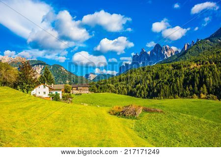 The valley is surrounded by a dentate wall of dolomite rocks. Warm autumn in the Dolomites, the Val de Funes. The concept of ecological tourism