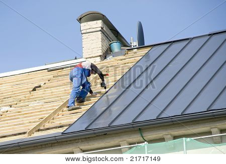 The Roofer Behind Work On Repair A Roof