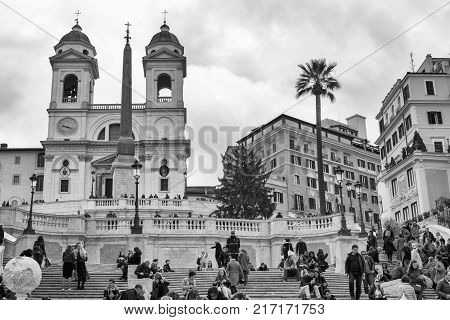 ROME, ITALY - November 2017: Tourists sat on Spanish Steps, Scalinata di Trinita dei Monti, one of most famous staircases in world above Piazza di Spagna and church Santissima Trinita dei Monti.