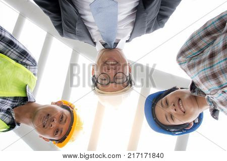 Professional Asian engineering team wearing safety helmet looking at camera from lower angle view at construction site