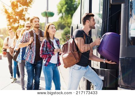 A group of tourists enters the bus. The guy helps the girl to bring the luggage to the bus. They will travel on a modern black bus. Behind them is a group of tourists with luggage.