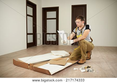 Carpenter checking assemble paper manual. Assembly forniture instructions