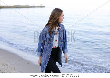 Attractive young woman walks slowly and walks along sea shoreline and examines neighborhood of beach with smile on face. European-looking girl with medium-length blond hair dressed in black pants, white T-shirt with bright pictures