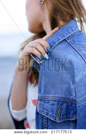Shooting close-up portrait of wonderful young woman who stares into distance at sea waves and flirtatiously beckons with look, poses and smiles, enjoys fresh air, standing on shore of blue bottomless sea on summer sunny evening.