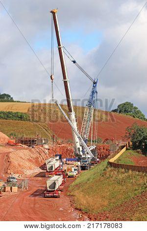 Mobile Crane lifting a bridge beam on a road construction site