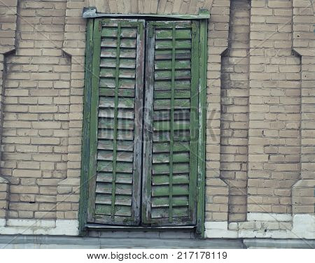 Old vintage retro wooden green cracked paint window blinds, as historic architecture background