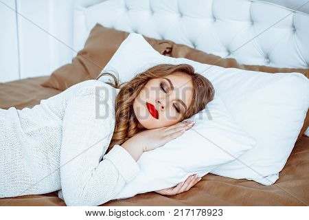 Beautiful young woman sleeping while lying in bed comfortably and blissfully. Sunbeam dawn on her face poster