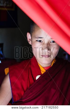 Paro, Bhutan - September 17, 2016: Young Bhutanese Monk Holding Buddhist Scripture Leaning To The Mo