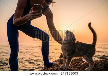 Young Yoga Woman in Bodysuit Having Fun With a Cat on the Beach at Amazing Sunrise. Making Selfie on Smartphone With Cute Cat