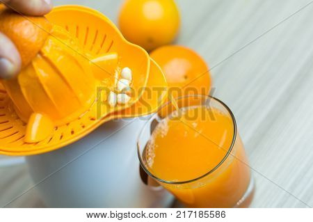Awesome Woman In The Kitchen Squeezing Fresh Orange Juice With An Electric Juicer.