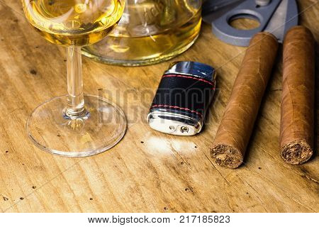 Cigar with bottle and whiskey glass lighter and cigar cutter on an old wooden board