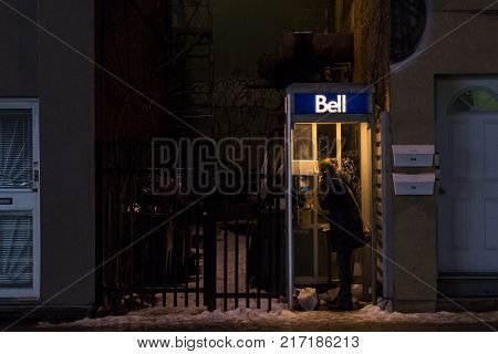 MONTREAL CANADA - DECEMBER 24 2016: Woman using a Bell Canada Payphone in Montreal in the evening under heavy snow. Bell Canada is one of the main phone booth providers and telephone carrier in the country