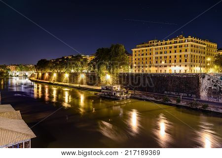 Rome, Italy - August 23, 2016: Tiber river in Rome at night. Long exposure photo