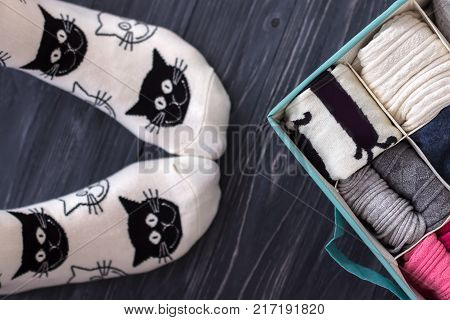 Feet selfie with black and white socks and a socks organizer on a dark wooden background. Top view