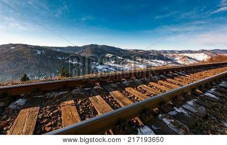 Railroad In Mountains With Snowy Slopes