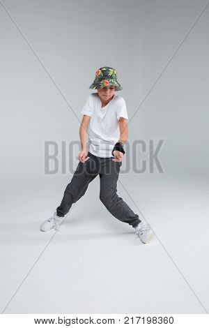 A young boy in a panama dance break dance dance his legs in knees in different directions on a gray background