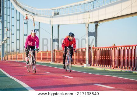 Two Young Female Cyclists Riding Road Bicycles on the Bridge Bike Line in the Cold Sunny Autumn Day. Healthy Lifestyle Concept.