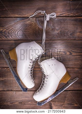 white leather skates hanging on a nail against a brown wall background