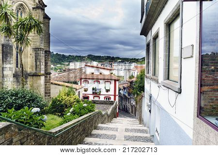 Street formed by stone stairs with a very colorful house and a sky with clouds threatening rain in Betanzos Galicia Spain