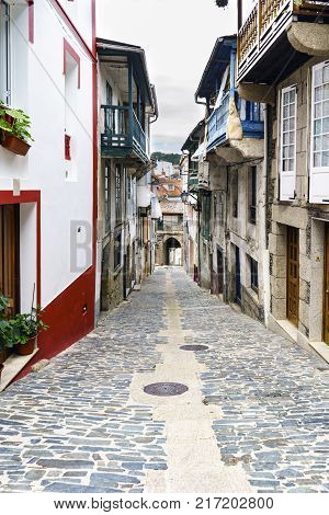 Typical street of a village of galicia on and finished in an arch with the stone floor and old houses in a village called Betanzos in Galicia Spain